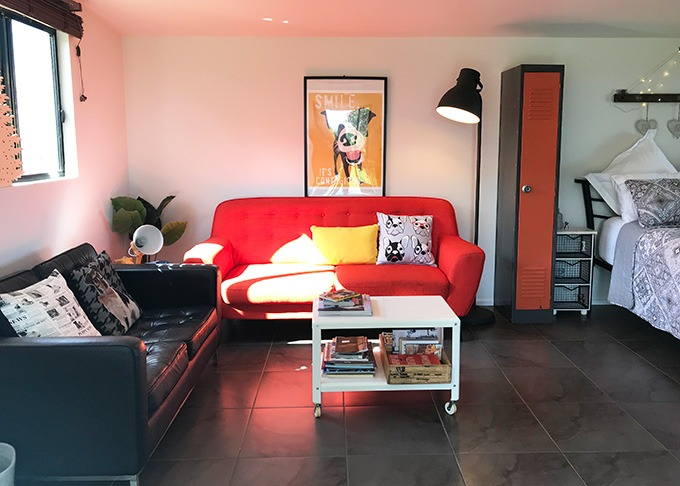 lounge room with red sofa, dog print on wall, white table, stand light and cupboard at the dog house port macquarie