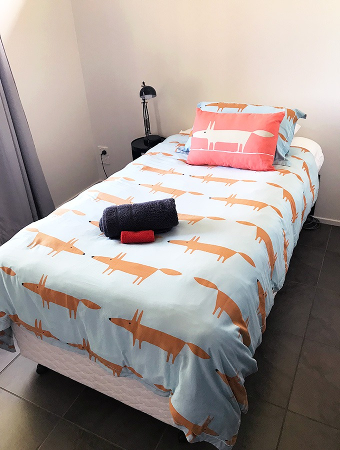 one of the single beds in the second bedroom of the dog house port mqcquarie