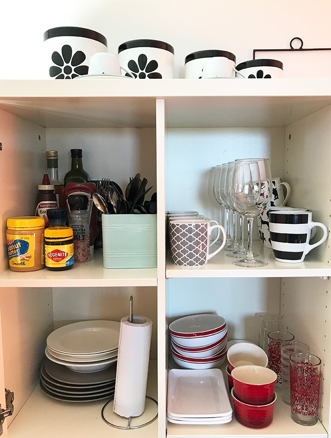 open cupboard in kitchen with cups, glasses, plates, bowls and condiments, at the dog house port macquarie