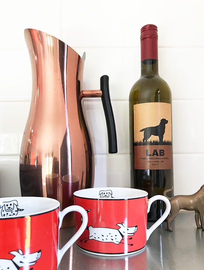 copper water jug, bottle of red wine with dog log, two red coffee cups with dogs on them at the dog house port macquarie