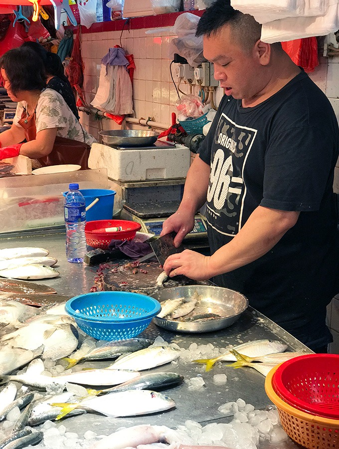 fishmonger preparing fish for his patrons at the red market macao
