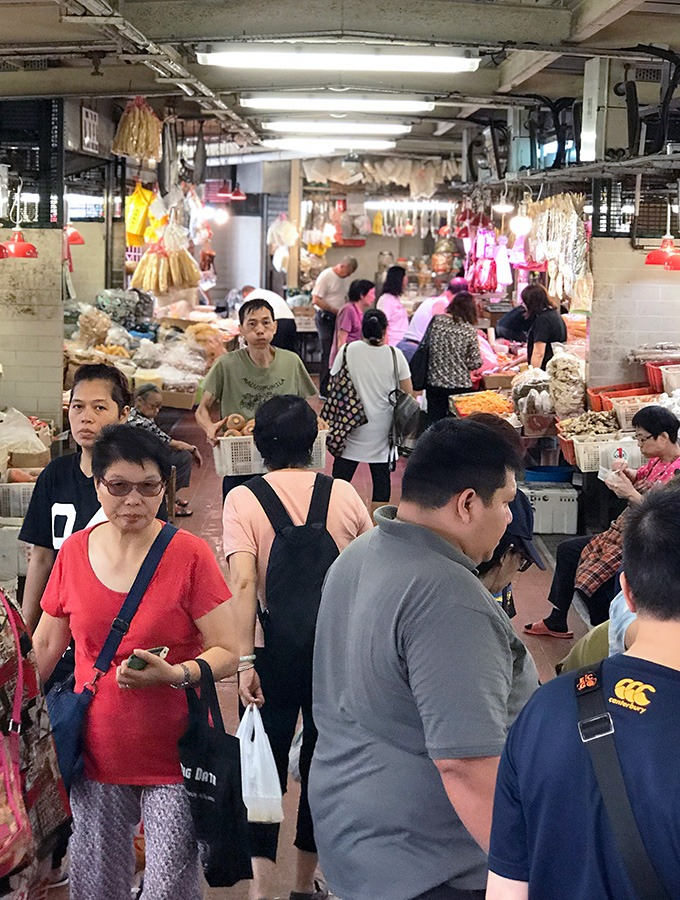 people walking around the vegetable hall of the red market macao