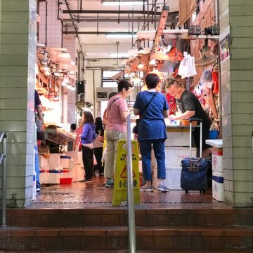 people standing at the top of a staircase looking at seafood to purchase at the red market macao