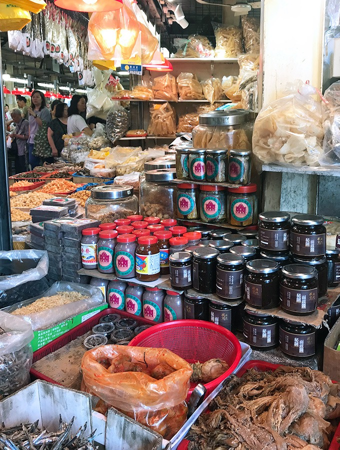 various sauces and dry foods on display at a market stand at the red market macao