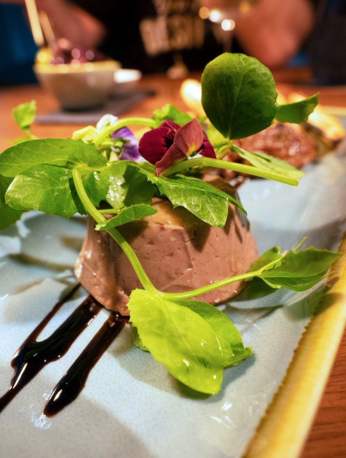 kangaroo rillette on a long white place with green leaves sitting on top of it