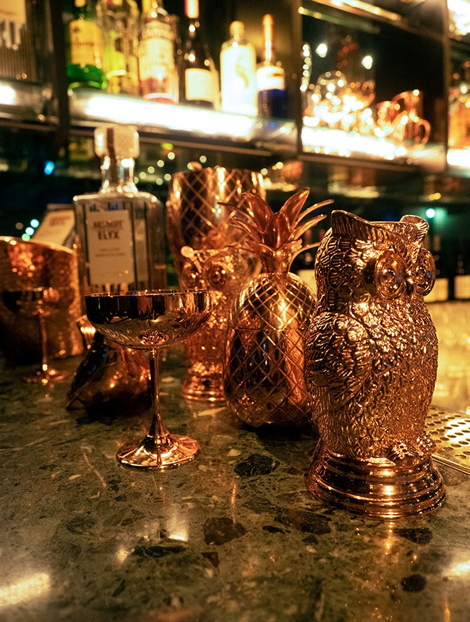 various copper mixology items on a bar