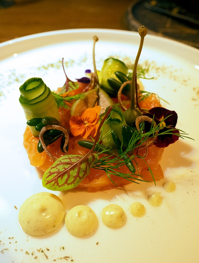 cured salmon on a plate with curls of cucumber, caperberries, flowers, micro herbs and dots of aioli at the front