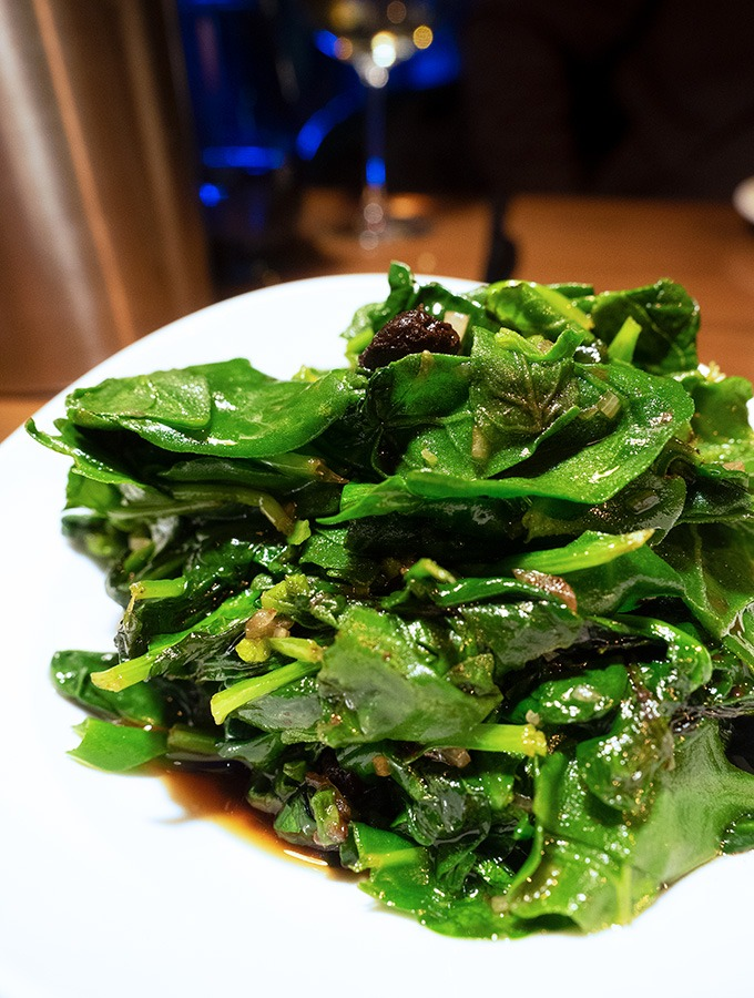 stir fried warrigal greens on a white plate