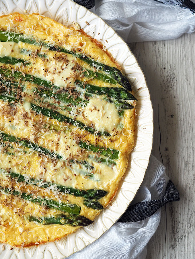 above view of asparagus frittata on a white serving plate