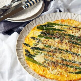 above view of asparagus frittata on a white serving plate with smaller serving plates and cutlery