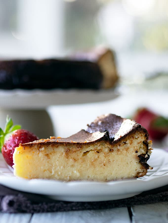 a slice of basque burnt cheesecake on a small plate with a strawberry and the whole cheesecake on a cake stand in the back ground.