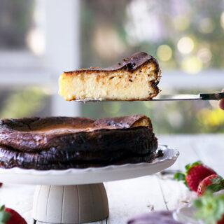sicde view of basque burnt cheesecake on a cake stand with a slice being removed