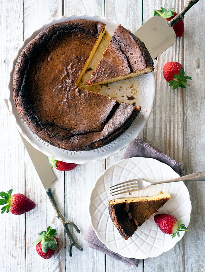 above shot of basque burnt cheesecake on a white serving dish with a slice removed and placed on a smaller plate. Strawberries are scattered around