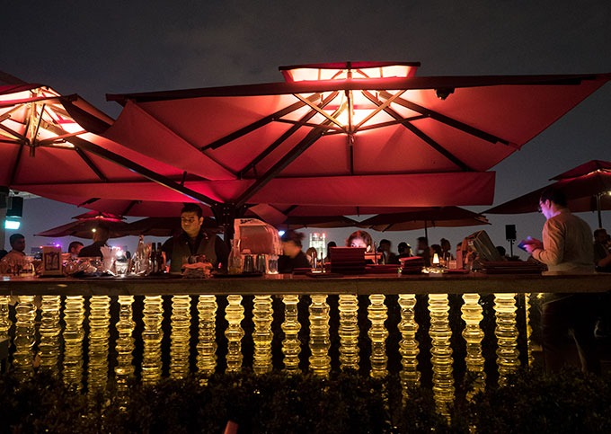bar with a big red umbrella over the top at night - Ce La Vi Singapore