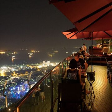tables and umbrellas on the 57th floor of marina bay sands looking out on the view of singapore at night
