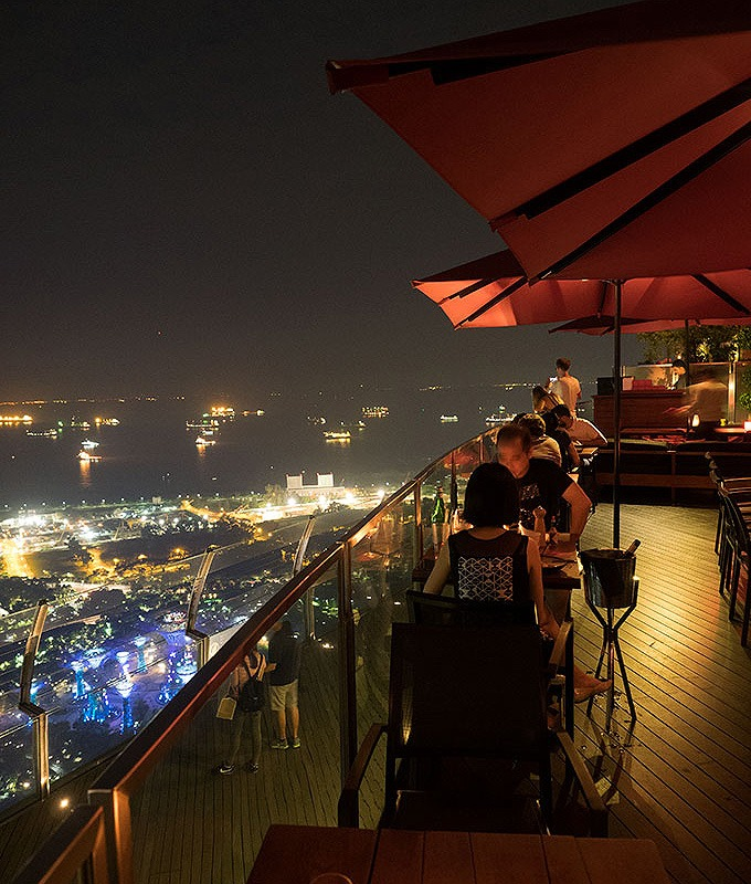 tables and umbrellas on the 57th floor of marina bay sands looking out on the view of singapore at night Ce La Vi Singapore