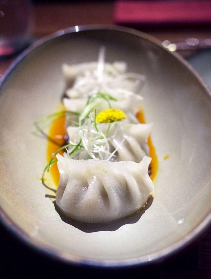dumplings on a plate with sauce - Ce La Vi Singapore