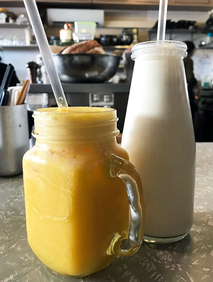 glass of orange juice and caramel milkshake in a bottle