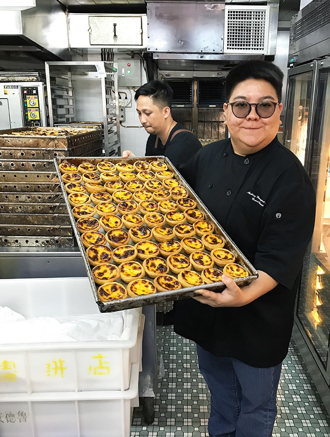 audrey stow holding a tray of macanese egg tarts in her bakery