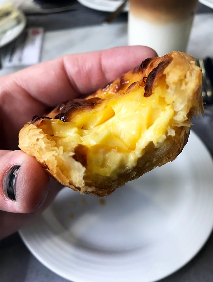 macanese egg tart being held with a bite taken out of it showing the custard