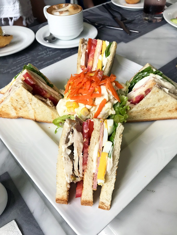 club sandwich cut into four triangle pieces on a white square plate