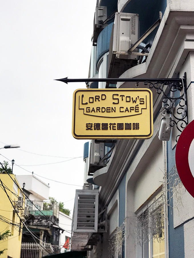 Lord Stows cafe sign hanging from an iron bar attached to the side of a building