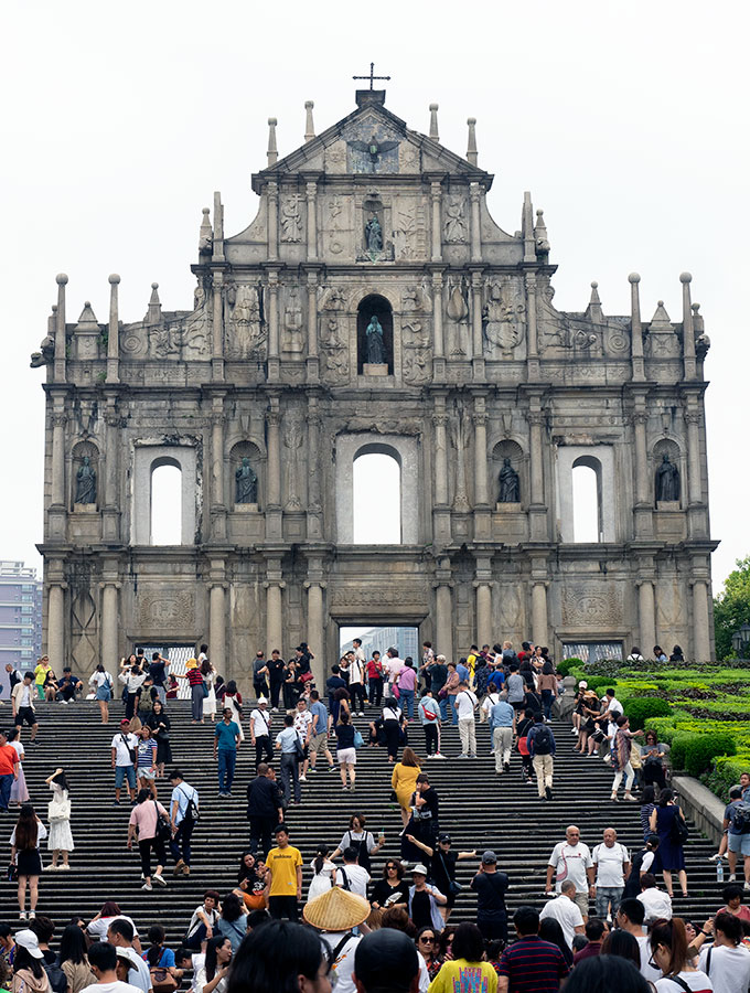 front view of the ruins of St Paul in Macao with people on the steps in front