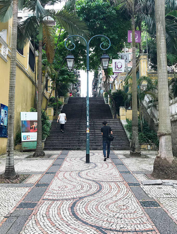 tiled street in Macao leading up to a set of stairs with palm trees either side