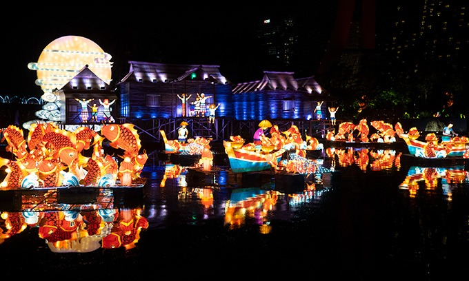 lanterns of fish, boats and houses lit up on the water