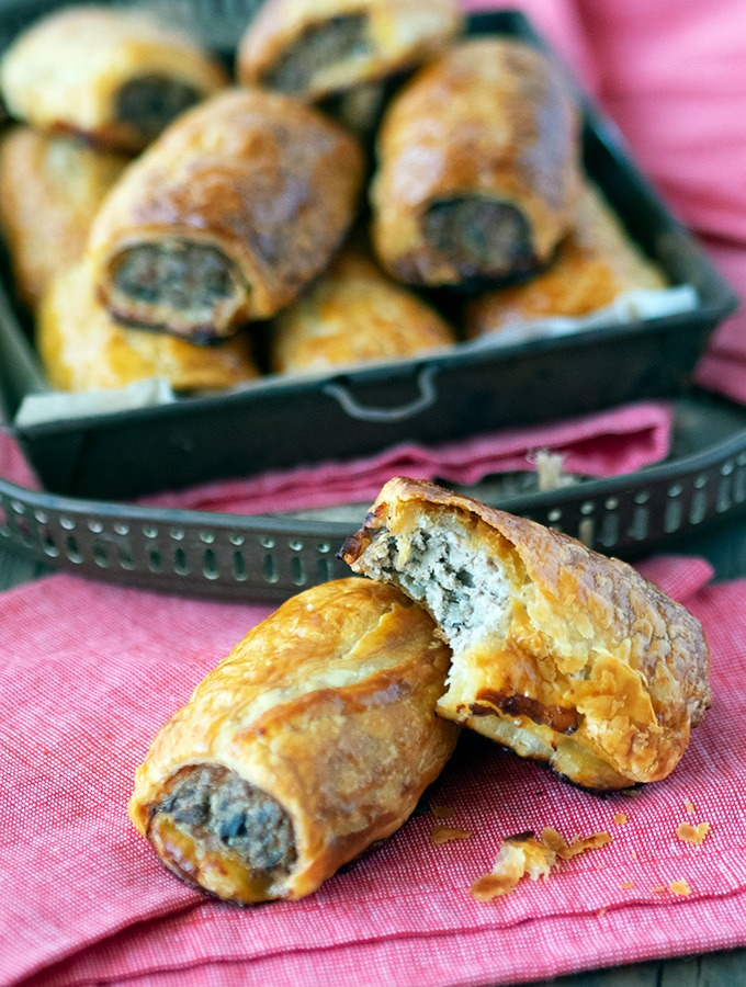 sausage rolls in a metal tray with two sausage rolls in front, one has a bite taken from it
