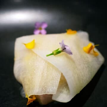 a parcel of mackrel inside ribbons of daikon with flowers on top at bangalay dining