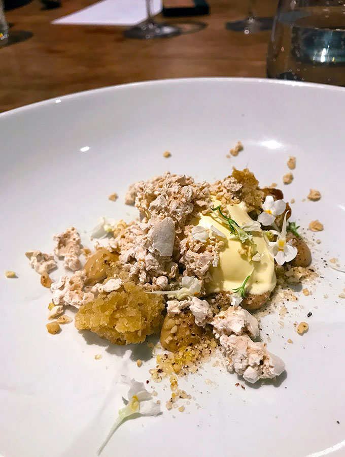 wattleseed ice cream with macadamia and caramelised white chocolate on a plate with edible flowers at bangalay dining