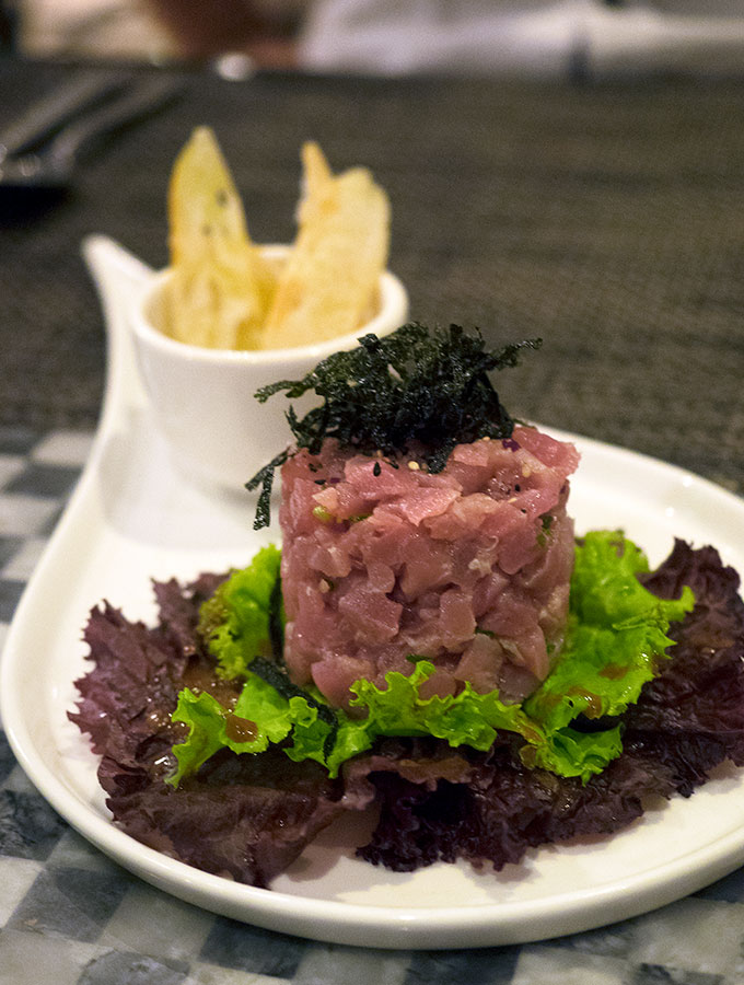 tuna tartare topped with nori and a side of crisp bread