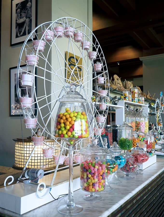 candy bar with various candies in glass jars and a ferris wheel
