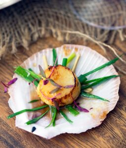 a single seared scallop with sake butter sauce on the shell