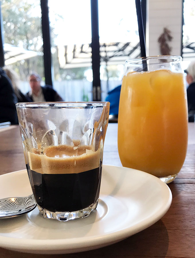espresso in a glass and an orange juice