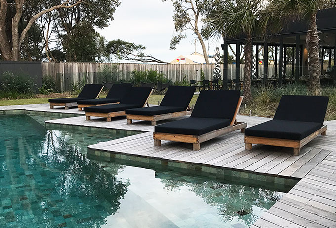 pool lounge recliner chairs with black cushions next to the pool