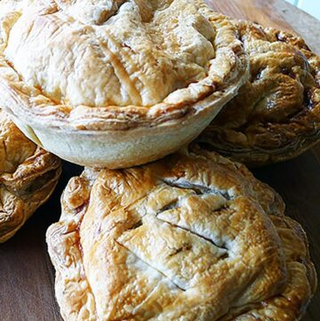 whole chicken leek and mushroom pies on a wooden board