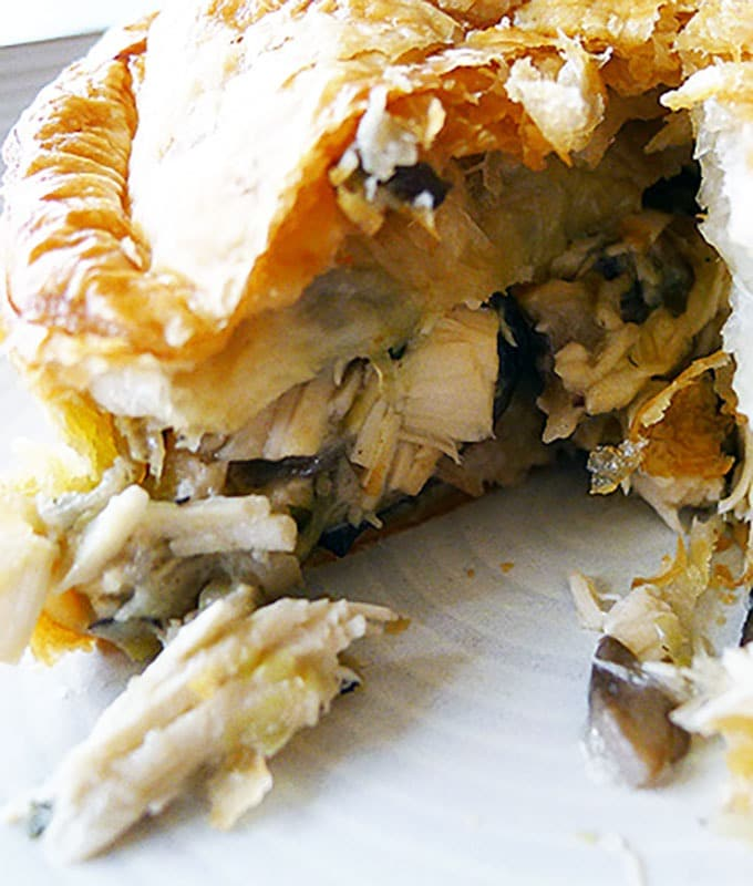 A pie cut in half to show the chicken, leek and mushroom filling