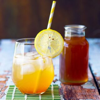 glass with a slice of lemon containing cola soda with a bottle of cola syrup next to it