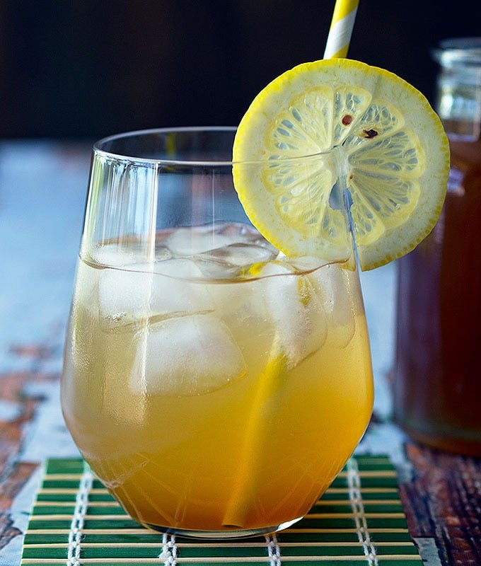 glass containing cola soda with a slice of lemon on the rim and a straw