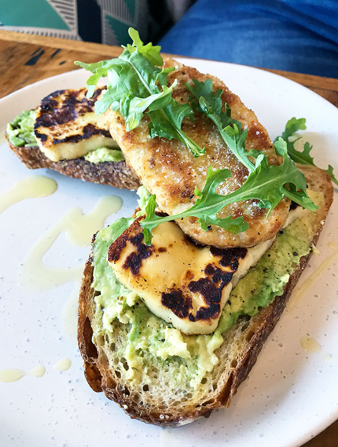 avocado on toast with haloumi and a hash brown on top