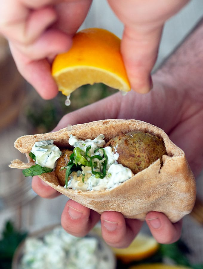 lemon being squeezed into a pita bread pocket with falafel