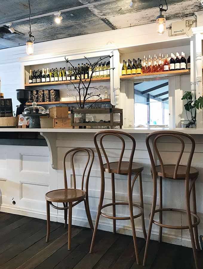 the bar at queen street eatery in berry with chairs, coffee machine and wine bottles behind