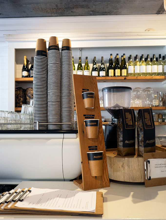 coffee making machine on the bar with various take away cups and bags of coffee
