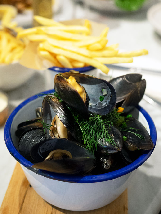 mussels in a blue rimmed bowl with fries in the back ground