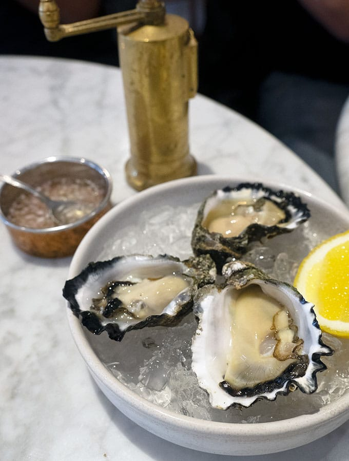 fresh oysters in the shell on a bowl of ice with a slice of lemon