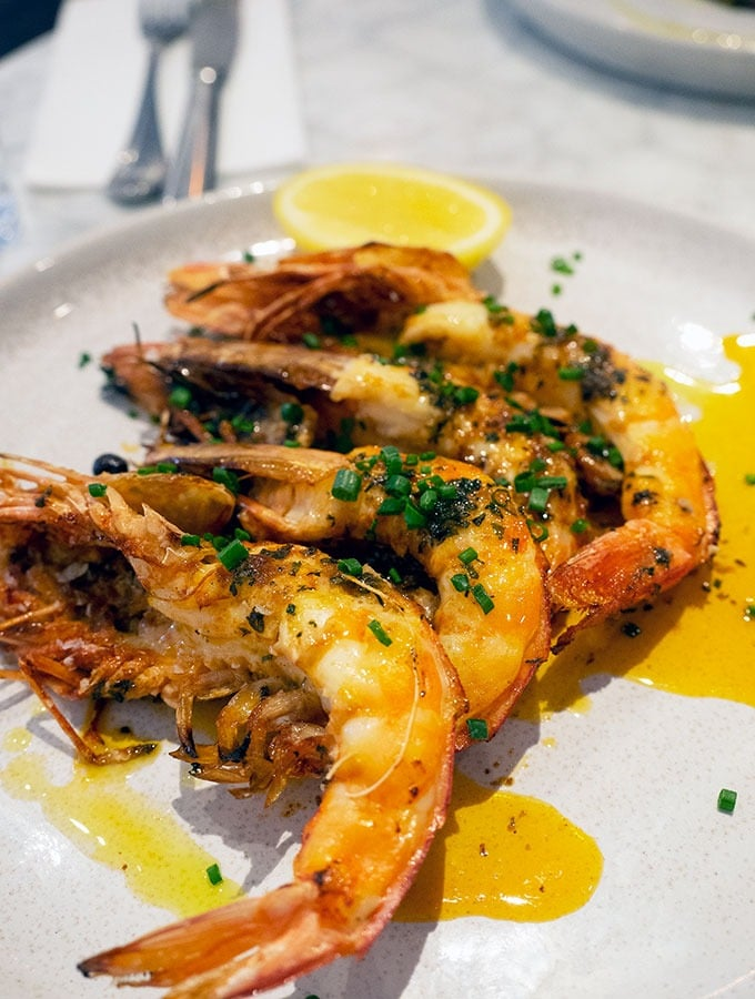 grilled large prawns on a plate covered with a sauce and a slice of lemon at the back