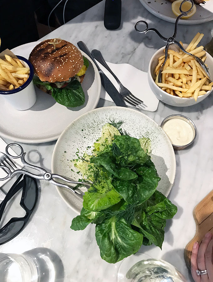 top view of dishes on the table, including a hamburger with chips, a green leaf salad, and a bowl of fries