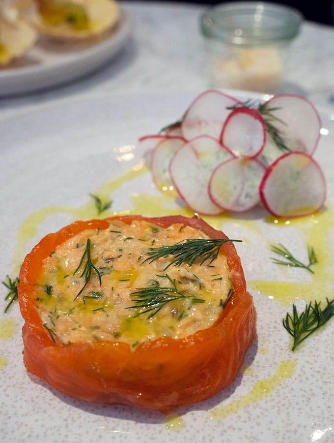 salmon rillett wrapped by smoked salmon with herb cream at the back that has been decorated with thin slices of radish.